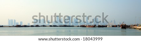 A panoramic view of the Dhow Harbour in Doha, Qatar, with the newly constructed high-rise area of the city in the haze behind - stock photo