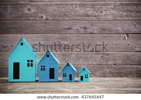 A paper houses stands over a wooden background - stock photo