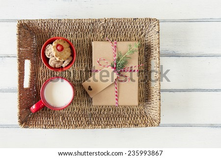 A paper parcel wrapped tied with a tag, shortbreads and a milk mug. A christmas gift box wrapped with paper kraft and tied with red & white baker's twine on a white wooden table. Vintage Style. - stock photo