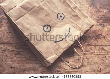 A paperbag with a smiling face painted on it lying on a wood table - stock photo