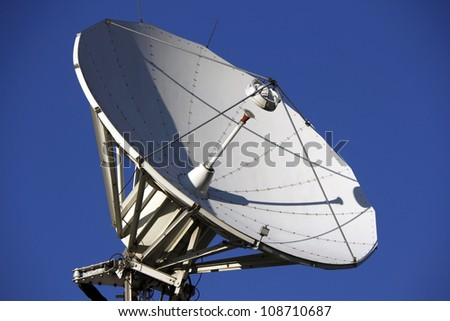 A parabolic satellite dish with blue sky and sunny day - stock photo