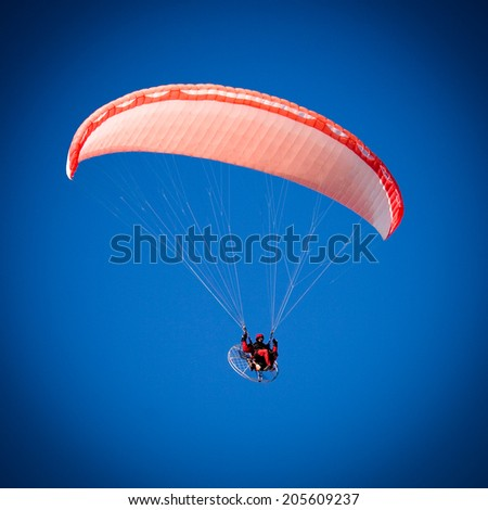A Paraglider flies in the blue sky - stock photo