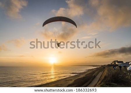 A paraglider flying over a beach in Bournemouth,Dorset,UK. - stock photo
