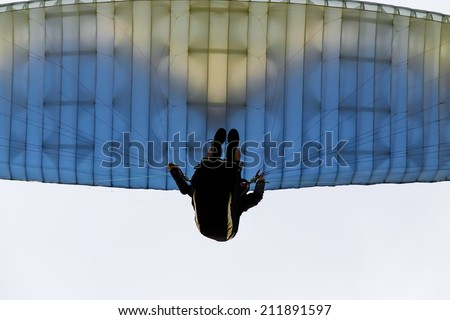 A paraglider soars in the sky at sunset - stock photo
