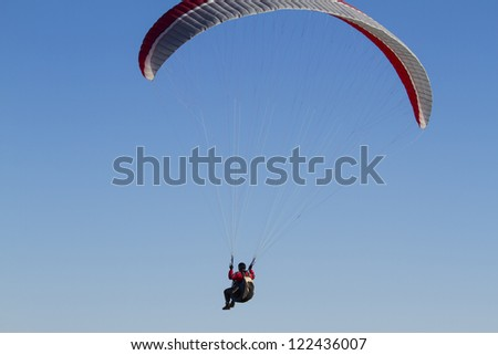 A paraglider takes to the sky. Shot from below against a blue sky. - stock photo