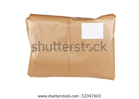 A parcel wrapped in brown paper and tied with rough twine, isolated on white background. Shallow depth of field - stock photo