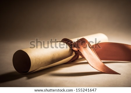 A parchment diploma scroll, rolled up with red ribbon laid at an oblique angle.  Processed to give a vintage or retro appearance. - stock photo