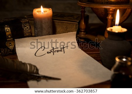a parchment paper with a quill and ink, candles and medieval decoration, concept contract - stock photo