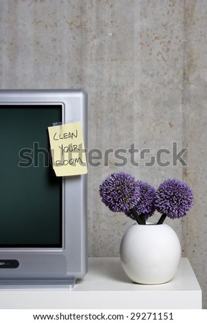 A parents' note to their children left on the television telling them to do their chores before watching a TV program. - stock photo