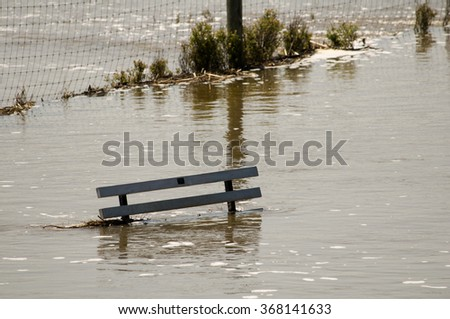 A park bench flooded by a river overflowing its banks. - stock photo