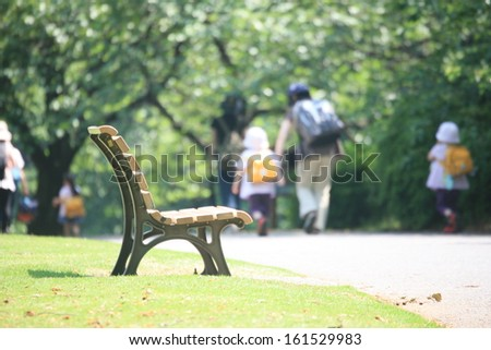 A park bench in the sunlight with many people walking nearby. - stock photo