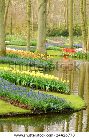 A park in springtime with water, trees and lots of flowers. - stock photo