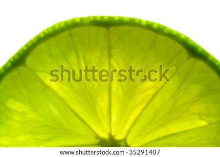 A part of a green lime slice, back lit and isolated on white background. - stock photo