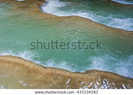 A part of beautiful clean green water from Kuang Si Waterfall (Tat Guangxi), Luang Prabang, Laos. blurred image from natural moving flow of water - stock photo
