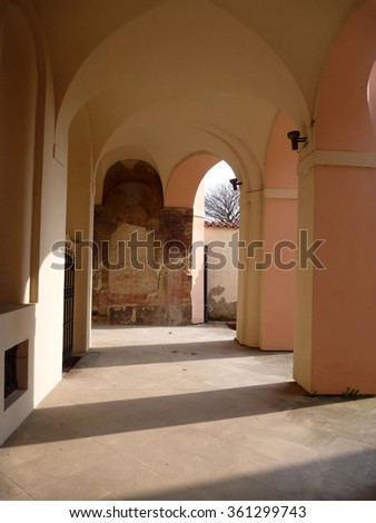 a pasageway in arcedes with shadow of columns - stock photo
