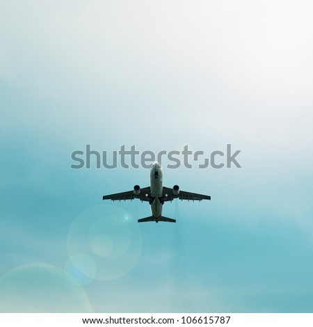 A passenger airplane flying in the blue sky - silhouette - stock photo