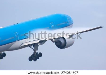 A passenger airplane is taking off from the runway. Notice the condensation over the wings. - stock photo