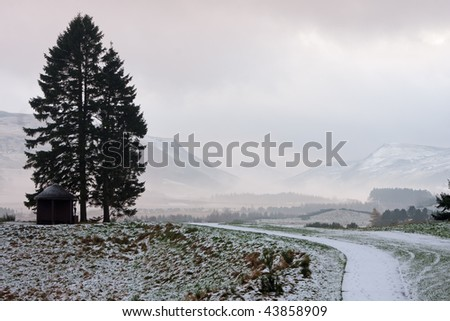 A path leading towards a background of mountainous scenery on a winter morning in Perthshire, Scotland. - stock photo