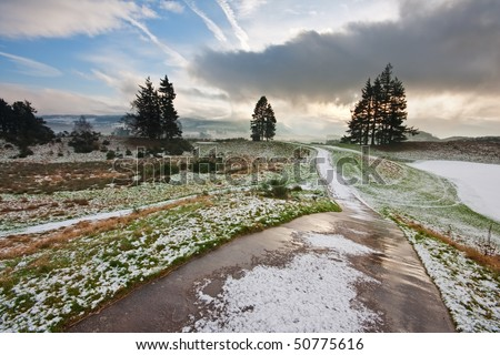 A path running through a snowy golf course on a winter morning in Scotland, with dramatic clouds in the background. - stock photo