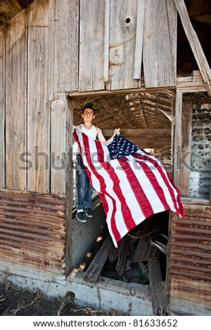 A patriotic teenager gets ready to hang an American flag on an old rustic barn - stock photo