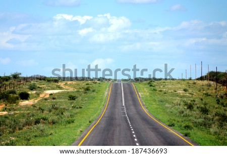 A paved road with green grass on the sides and blue sky above - stock photo