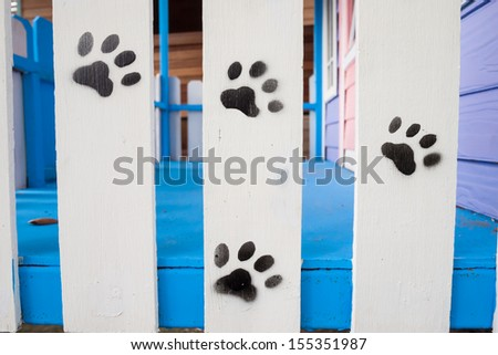A paw print painted on a wood fence - stock photo