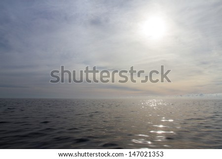 A peaceful ocean scene with sunlight reflecting across the ocean and dreamy clouds - stock photo