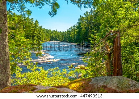 A peaceful scene of a river running from Cascade Falls in the Boundary Waters Canoe Area, in the remote North Woods of Northern Minnesota with blue skies and framed by trees. - stock photo