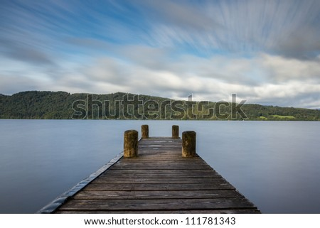 A peaceful wooden jetty on Lake Windermere with a foreboding yet dreamy sky - stock photo