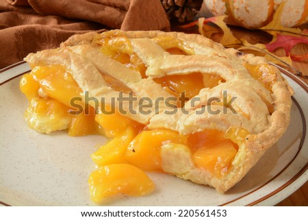 A peach pie with lattice crust on a holiday decorated table - stock photo