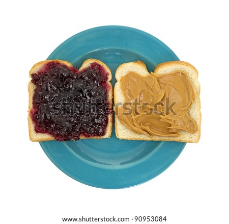 A peanut butter and jelly sandwich open faced on a blue plate. - stock photo