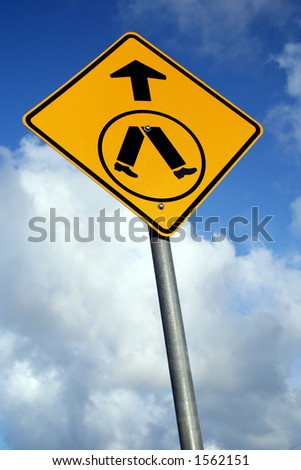 A pedestrian crossing sign against a blue cloudy sky - stock photo