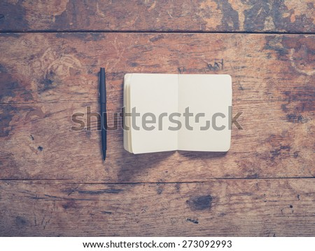 A pen and a small notepad on a wooden table - stock photo