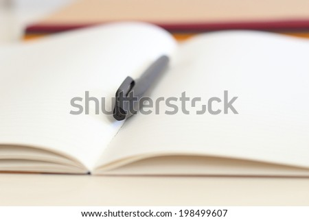 a pen and blank paper of open book - stock photo