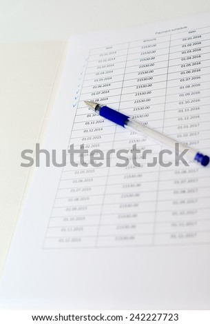 A pen lay on a payment schedule for the loan - stock photo