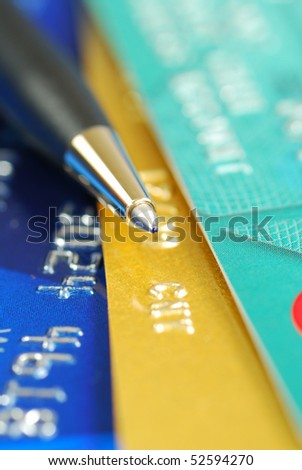 A pen on the top of several credit cards - stock photo