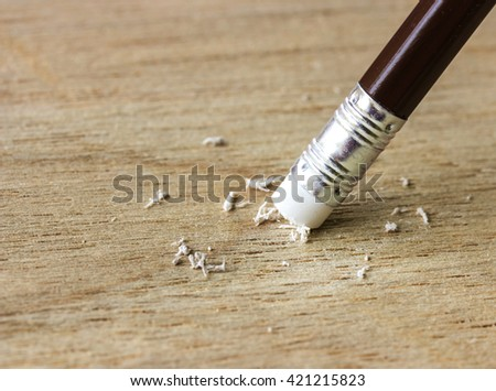 A pencil eraser removing a written mistake on wood - stock photo