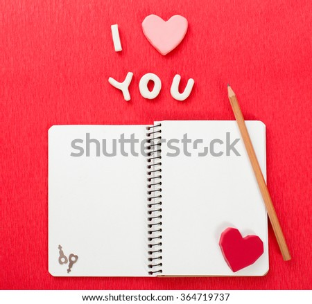 A pencil on a notebook and a red heart. Valentines day concepts - stock photo