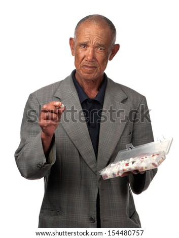 A pensioner grapples with all the tablets he has to take at this time of his life. - stock photo