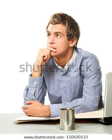 A pensive businessman sitting at a workplace, looking up - stock photo
