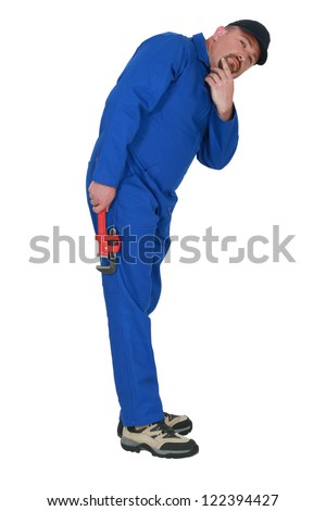 A pensive tradesman stooped over - stock photo