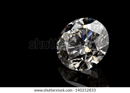 A perfect cut of diamond isolated on black background. - stock photo