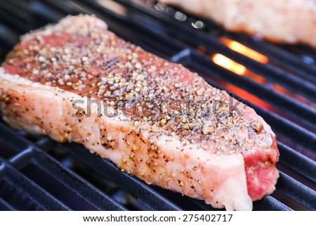 A perfect 1 inch thick New York strip loin steak, seasoned and grilling over the flame on the barbecue - stock photo