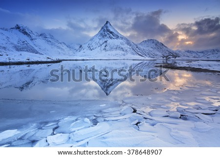 A perfect reflection of a mountain in the fjord below. Photographed on the Lofoten in northern Norway in winter. - stock photo