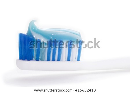 A Perfectly Curled Toothpaste Swirl Sits Atop a Toothbrush, a Reminder to Brush Your Teeth - stock photo