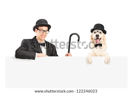 A performer in suit, retro hat and cane posing with dog behind a panel isolated on white - stock photo