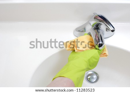 A person cleaning the bathroom sink with a glove - stock photo
