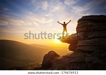 A person expressing freedom - reaching up into the sky against a sunset. - stock photo