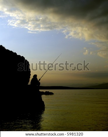 A person fishing on the beach at sunset - stock photo