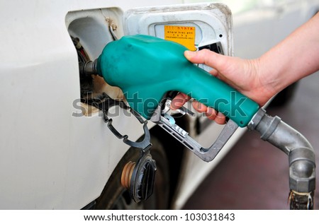 A person fuel his vehicle in a fueling station. - stock photo